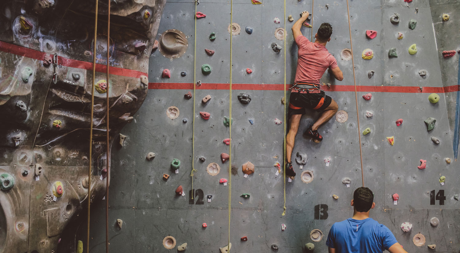 Two people climbing a climbing wall, one on the wall, the other guiding from below.