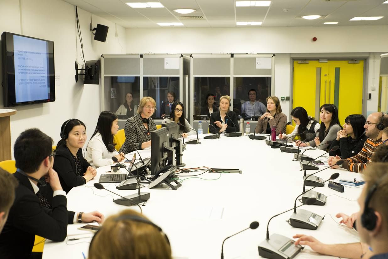 Students taking part in a mock conference within our interpreting lab - students sitting around a round table, with microphones and interpreting equipment