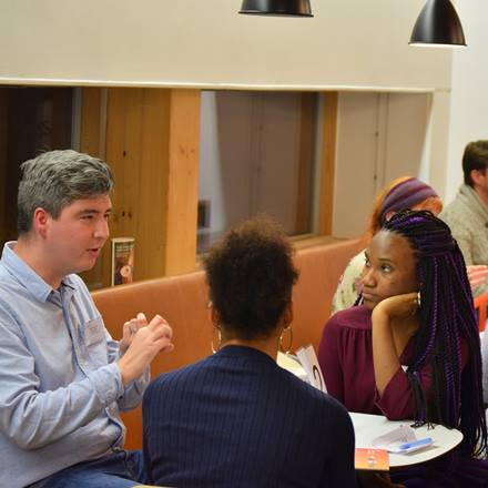 two students sit around a table discussing their career options with an Essex Alumnus