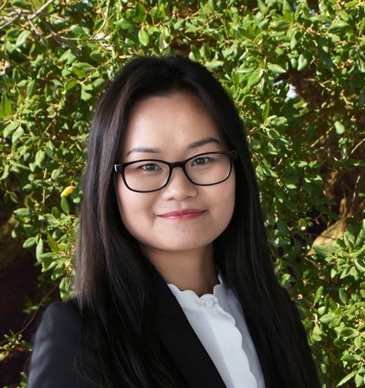 Quynh Nguyen stands in front of a foliage background