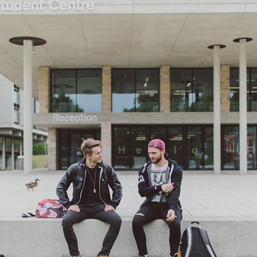 Two male students sitting outside the Silberrad Student Centre