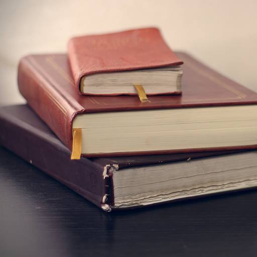 Three books in a stack on a desk