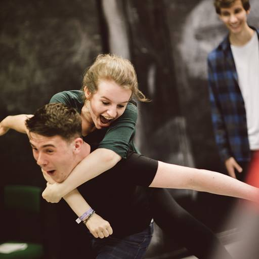 Female student jumping on the back of male student in a drama class