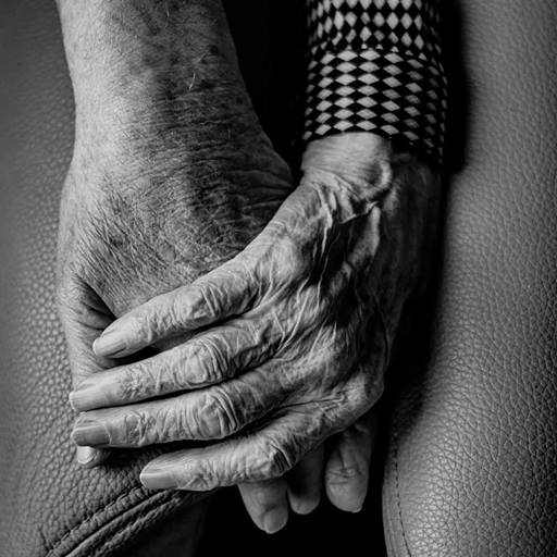 Two hands, one of an elderly person photographed in black and white