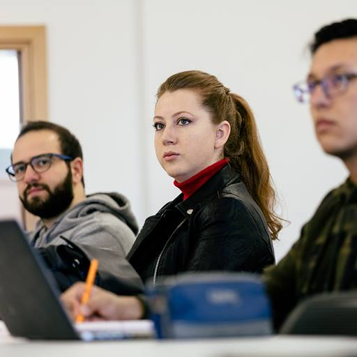 A female MBA student sits at a desk in a classroom flanked by two out of focus male students. She is paying rapt attention to the lecturer who is not pictured.
