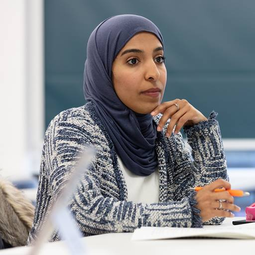 An Essex Business School student wearing a blue hijab headscarf sits in a classroom with a pen in her hand.