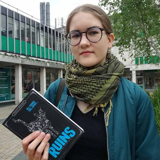 Ellinor Friström holding a copy of Ruins by Joshua Winnings