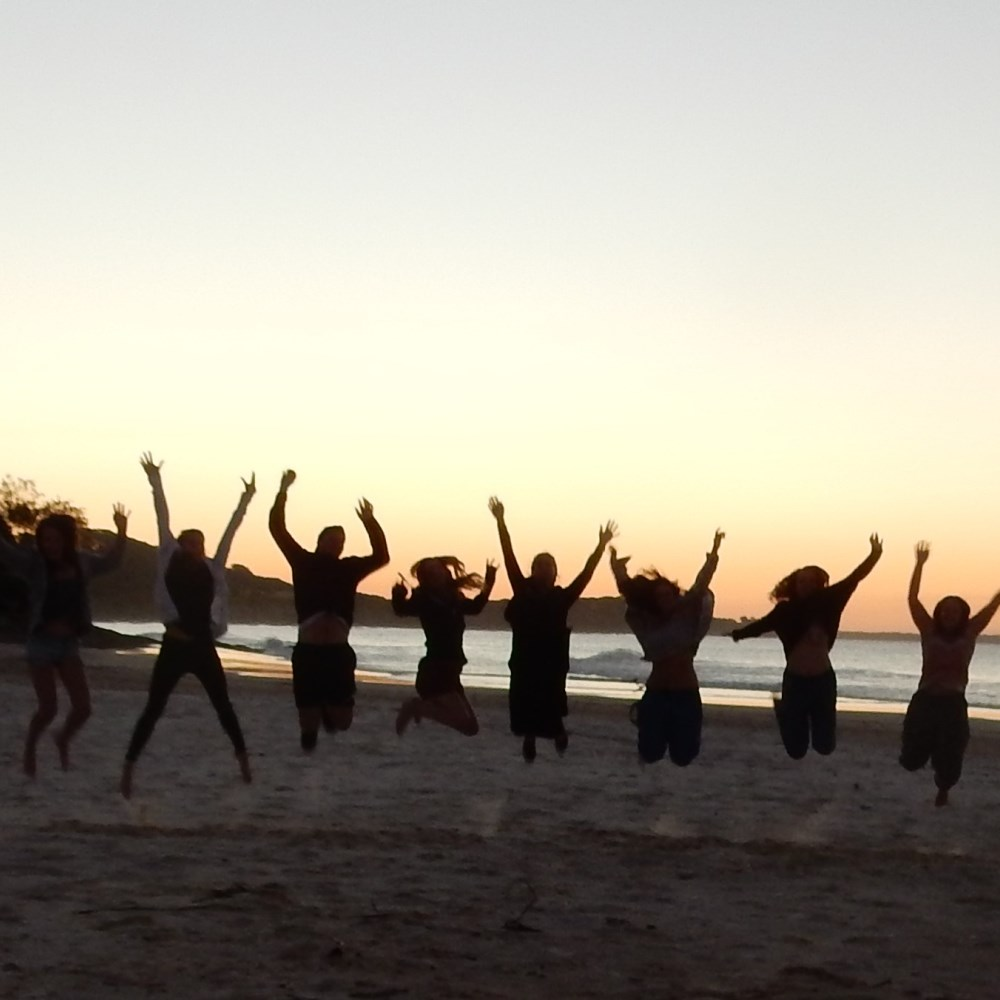 People on a beach jumping in front of sunset