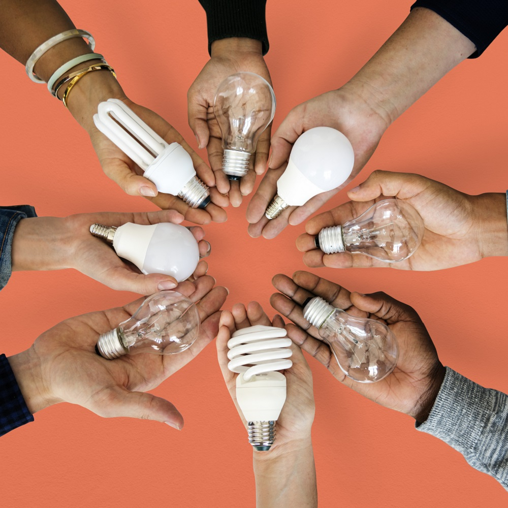 Eight people with their hands held out with different styles of light bulb in the palms of their hands on an orange background.