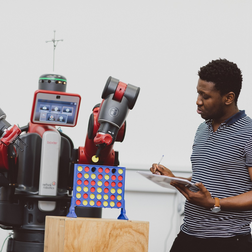 On the right a male student is holding a clipboard. On the left a Baxter robot is placing a yellow piece in a Connect Four game.