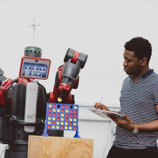 A young black man holding an iPad and stylus, standing to the right of a large red Baxter robot that is playing Connect-4.