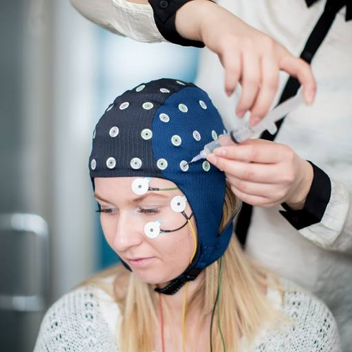 A woman wearing an EEG cap, her head turned away from the camera while another person adjusts the cap.