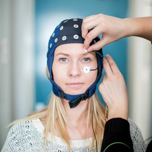 A woman wearing an EEG cap is looking directly at the camera, while a second person mostly out of shot on the right attaches a sensor to her face.