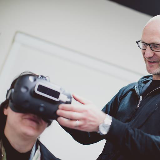 Professor Paul Hibbard stands on the right of the shot, his hands reaching out to adjust a VR headset that a person to the left of the photo is wearing.