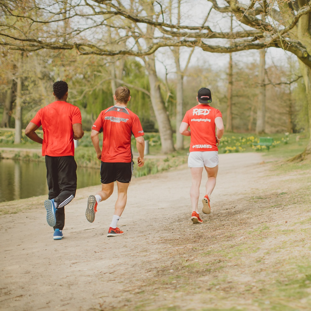 Three men in red t-shirts running along a path