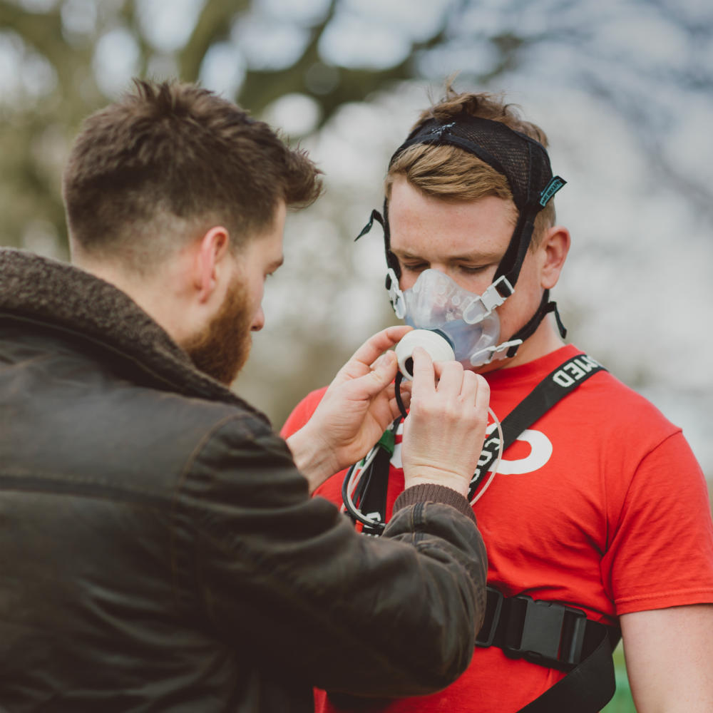 A researcher adjusts an oxygen mask worn by a person in a red t-shirt, who has some other equipment strapped around his chest.