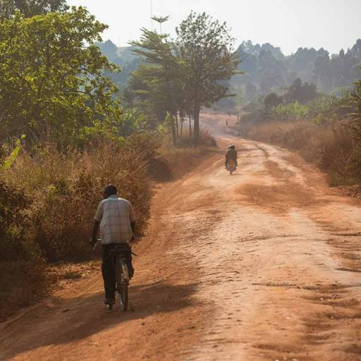 A dirt road in Uganda with cyclist travelling away into the distance.