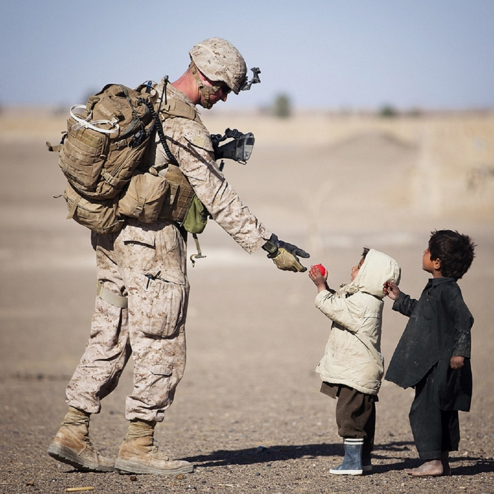 An allied forces soldier dressed in combat uniform , handing food to two small children in a desert
