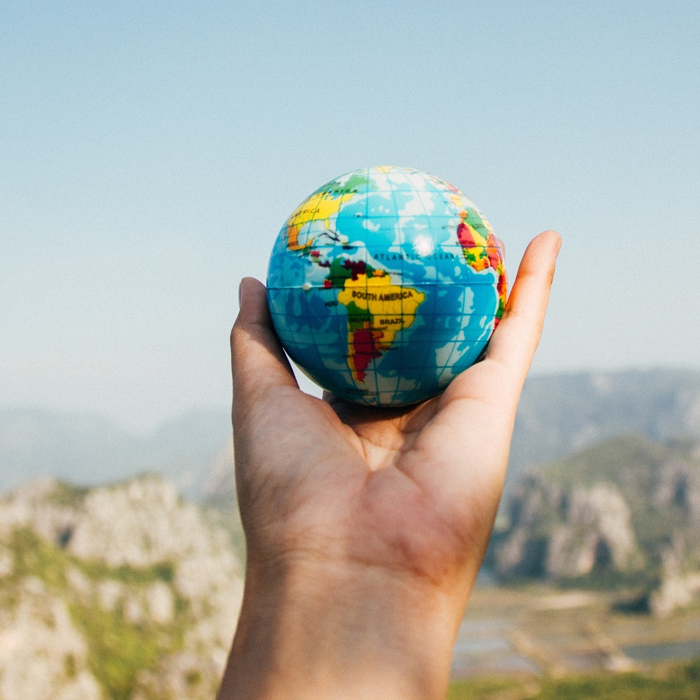 A small globe in the palm of a hand with mountains in the background