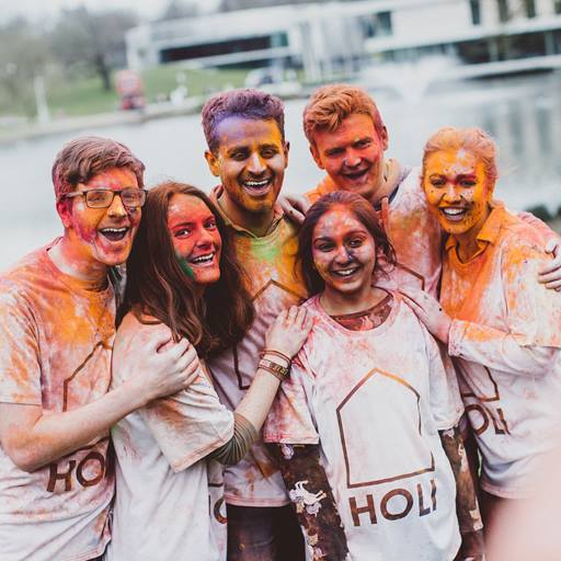 Students covered in holi-paint smiling