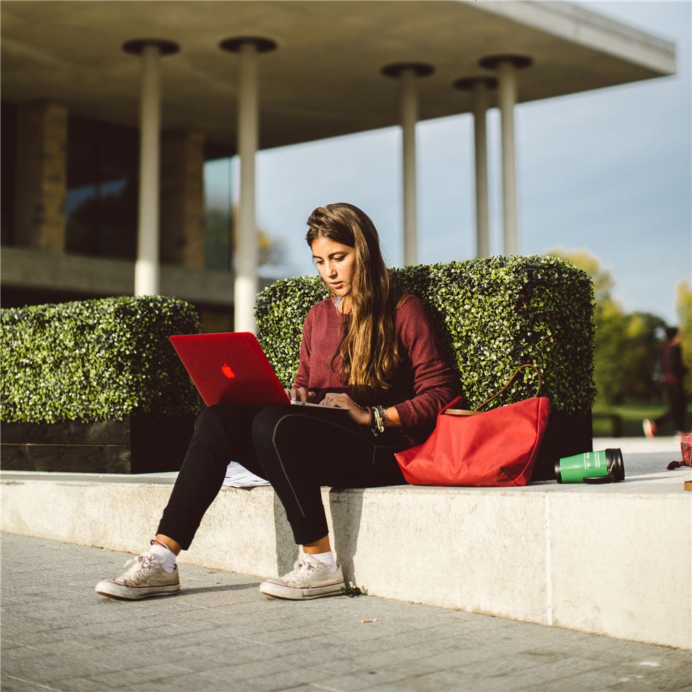 Student sitting outside Sierrbad on computer