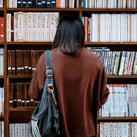 Person standing in front of bookcase