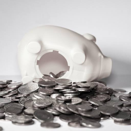 A white ceramic piggy bank turned upside down with coins everywhere.
