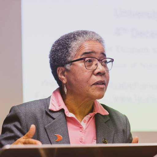 A head and shoulders photo of Dame Professor Anionwu delivering a talk at the University of Essex