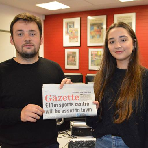 Two journalism students holding up a newspaper