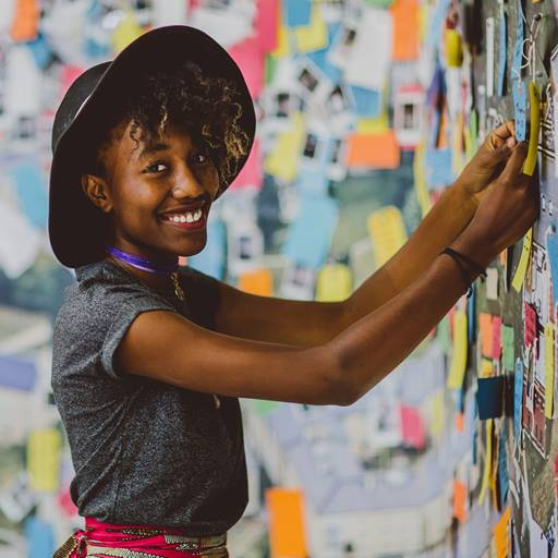 Young woman pinning a note to a wall covered in memos