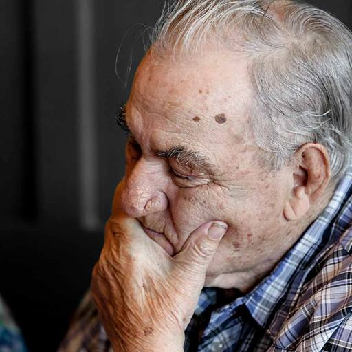 An elderly man resting his chin on his hand with his eyes closed