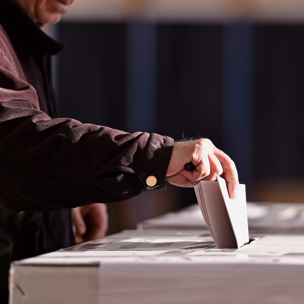 A man in a dark winter coat holding a ballot paper as he drops  it in the ballot box