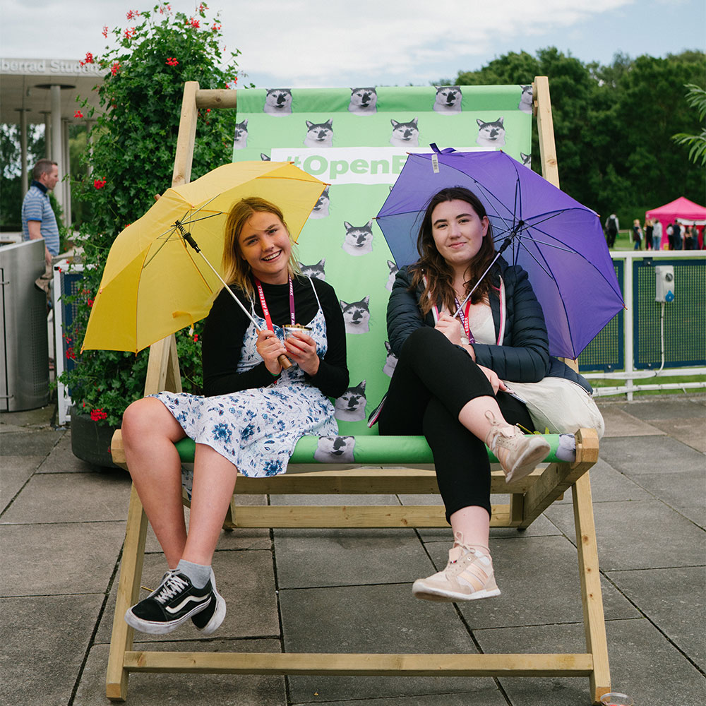 Two girls sitting on a giant armchair at an Open Day, each holding an umbrella