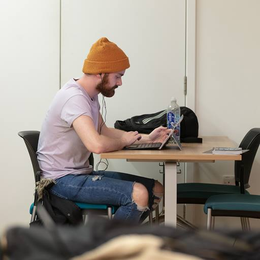 An Essex Business School student sits in a study pod with his laptop in the business school building