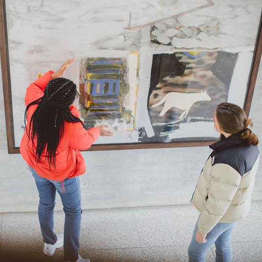 Students examining a piece of art hung on the wall