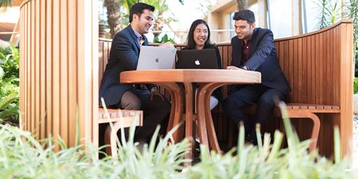 Three MBA Students sit around a table in the Winter Garden in discussion