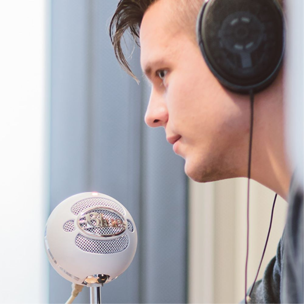 man wearing headphones speaking into microphone