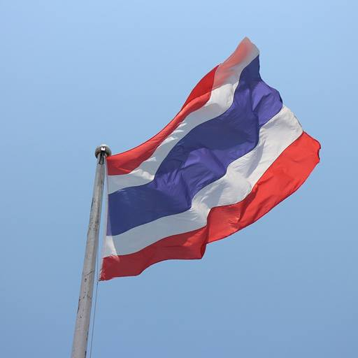 The flag of Thailand (red, white and blue horizontal stripes) flying against a blue sky.
