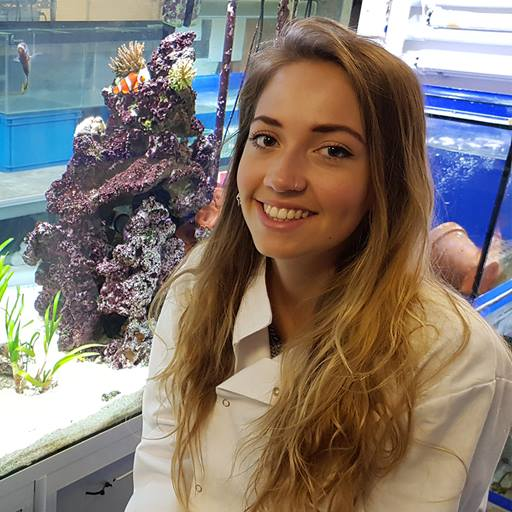 Harriet wearing a lab coat and sitting in front of a coral tank.