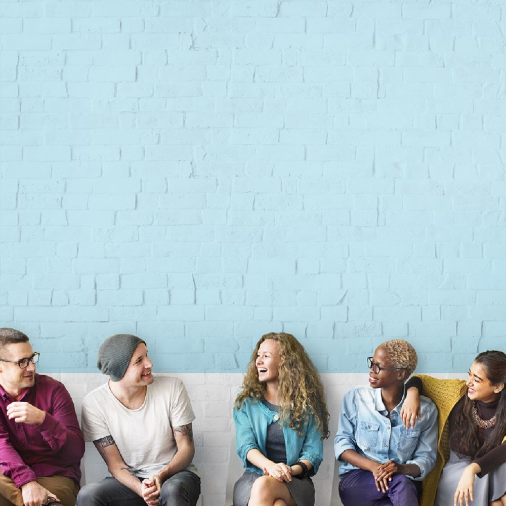 A group of friends sat in a line talking against a blue painted brick wall