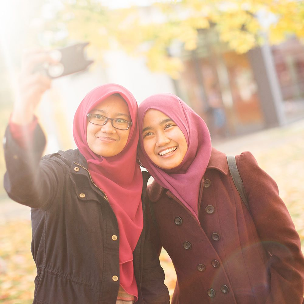 Two students taking a selfie with a mobile phone