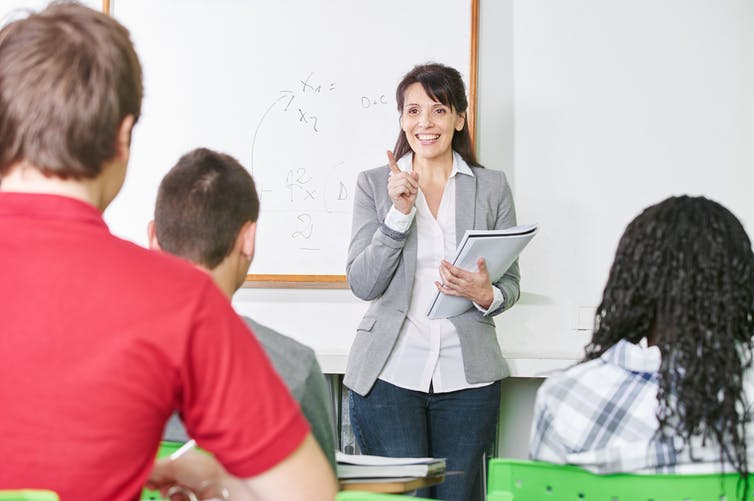 Female teacher in front of class of students