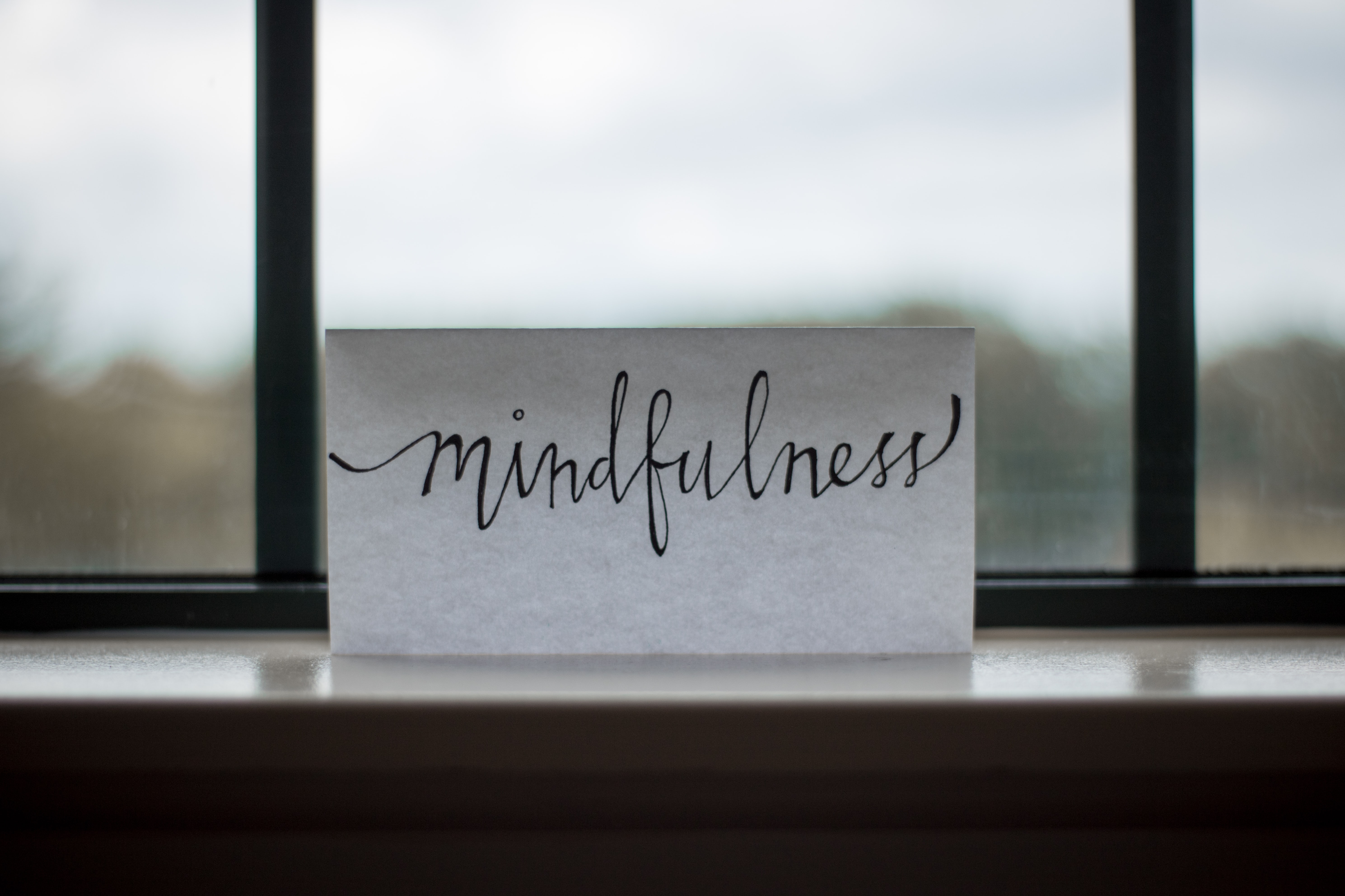 A sign with 'Mindfulness' handwritten on it in cursive script against a window