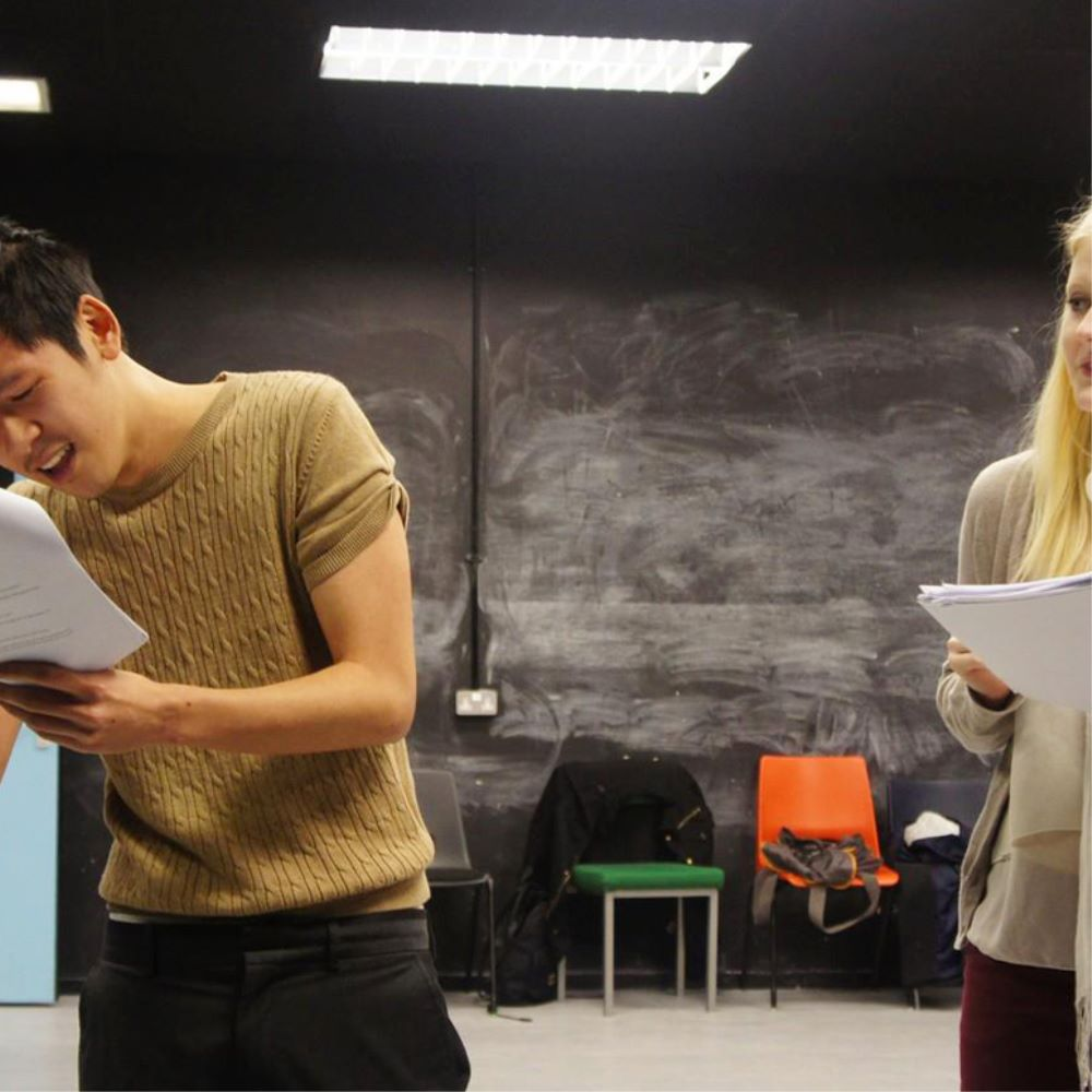 Drama students rehearsing with script