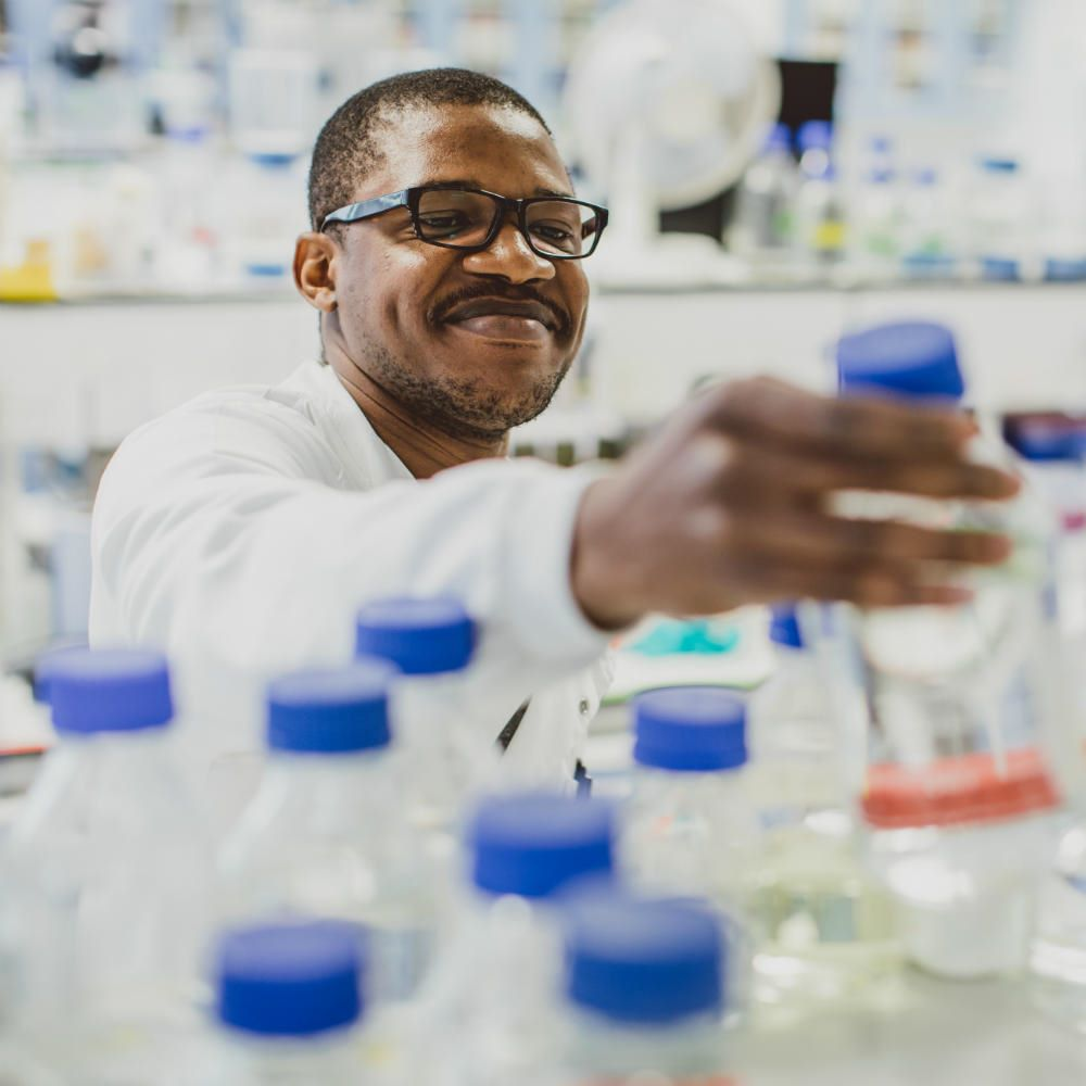 A man wearing a lab coat reaching across a laboratory shelf, picking up a clear bottle with a blue lid.