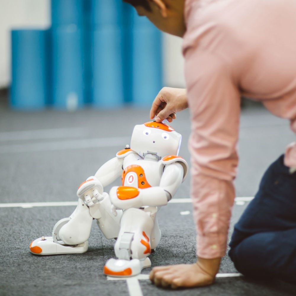 Image of a research student working with a Nao robot in our Robotics Arena.