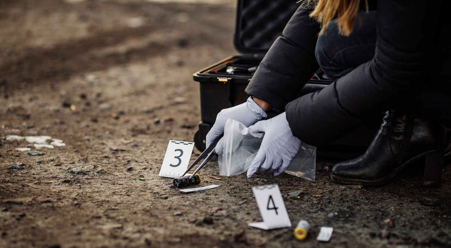 A woman collecting evidence from a crime scene