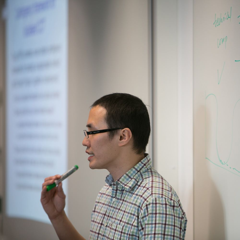 Lecturer standing next to whiteboard