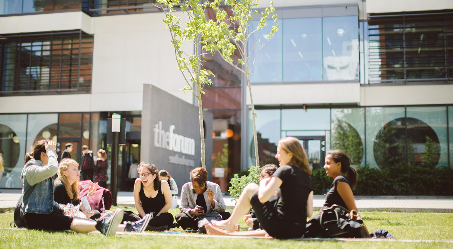 Students sitting on the grass outside The Forum