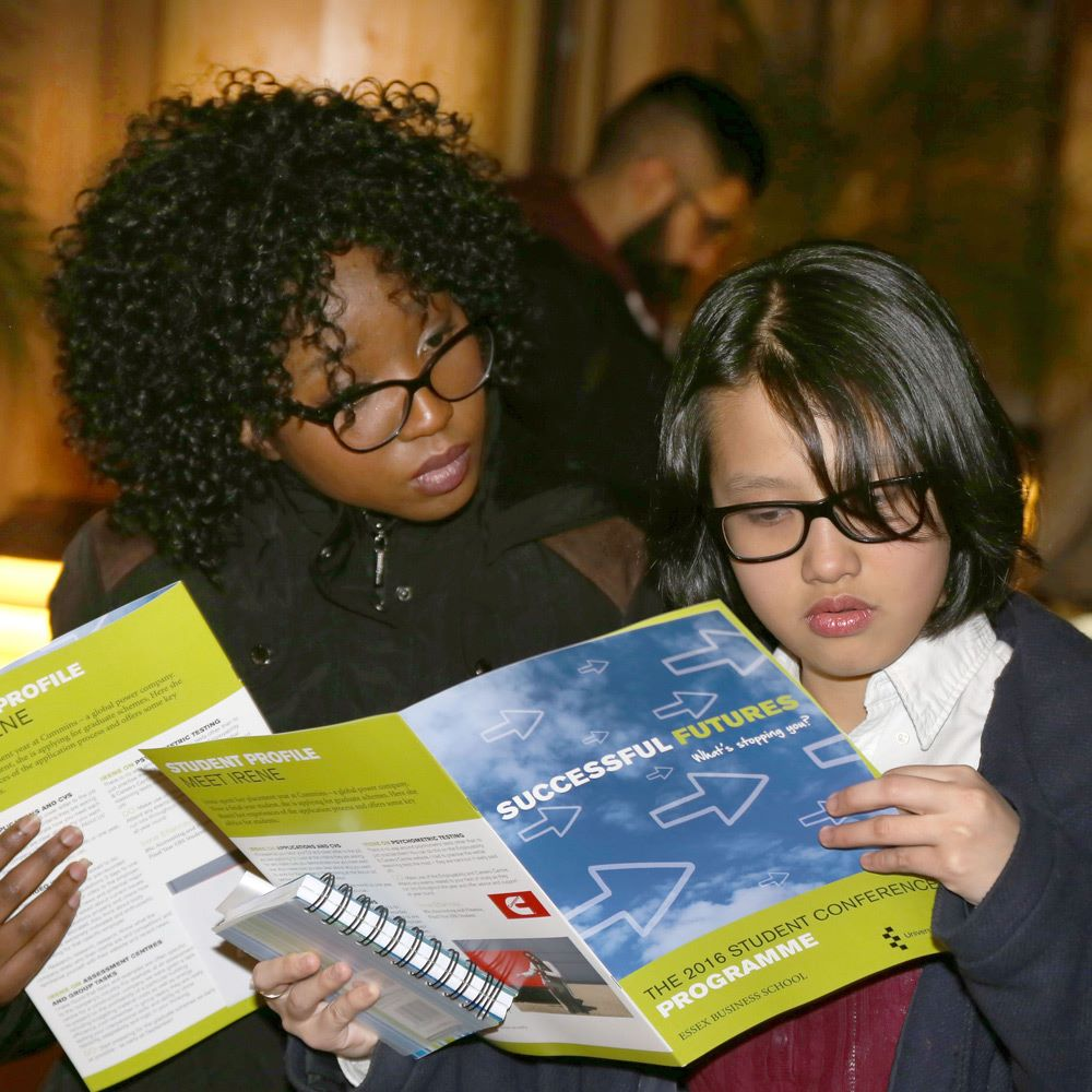 Students looking at programme for Successful Futures conference